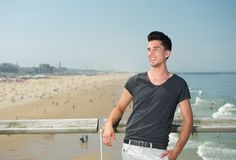 Homem novo feliz que sorri em férias na praia Fotografia de Stock Royalty Free