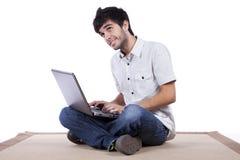 Homem novo feliz que surfa o Internet Fotos de Stock
