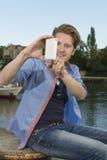 Homem novo feliz que toma imagens com telefone esperto Imagem de Stock Royalty Free