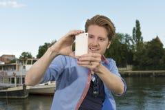 Homem novo feliz que toma imagens com telefone esperto Fotografia de Stock