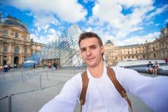 Homem novo feliz que toma uma foto do selfie em Paris Foto de Stock