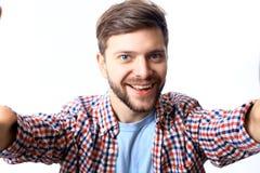 Homem novo feliz que toma uma foto do selfie Isolado no branco fotos de stock