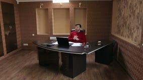 Homem novo feliz que trabalha no portátil ao sentar-se em seu lugar de funcionamento no escritório filme