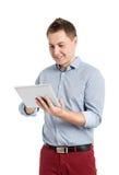 Homem novo feliz que usa a tabuleta de Digitas Imagem de Stock