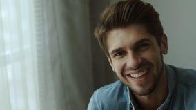Homem novo feliz Retrato do homem novo considerável na camisa ocasional que mantém os braços cruzados e que sorri em casa video estoque