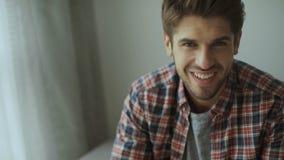 Homem novo feliz Retrato do homem novo considerável na camisa ocasional que mantém os braços cruzados e sorriso
