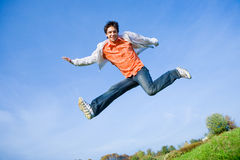 Homem novo feliz - saltando no céu azul Imagem de Stock