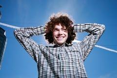 Homem novo feliz sobre o céu azul Imagens de Stock