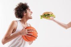 Homem novo fino com fome que guarda a bola foto de stock royalty free