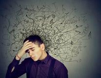 Homem novo forçado pensativo com uma confusão em sua cabeça imagem de stock