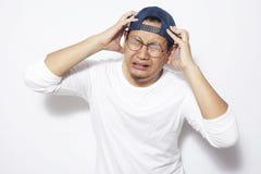 Homem novo forçado que tem a dor de cabeça fotografia de stock