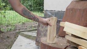 Homem novo forte que desbasta a madeira no quintal com machado - vídeos de arquivo