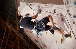 Homem novo forte que empurra-se mais altamente para alcançar dentro a parte superior da parede de escalada artificial no gym boul imagem de stock