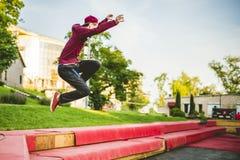 Homem novo freerun no corredor do parque público da cidade do verão, saltando e voando, conceito do parkour fotografia de stock royalty free