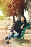 Homem novo fresco elegante que relaxa em um banco em um parque com árvores imagem de stock