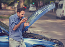 Homem novo frustrante que chama o auxílio da borda da estrada após a decomposição imagem de stock royalty free