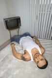 Homem novo furado que encontra-se na cama Fotografia de Stock Royalty Free