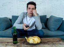 Homem novo furado que senta-se no sofá que olha os canais de comutação da tevê procurar esportes vivos imagem de stock royalty free