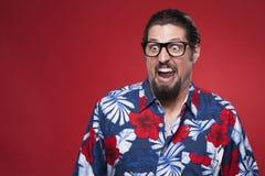Homem novo furioso na camisa havaiana com a boca aberta Fotos de Stock