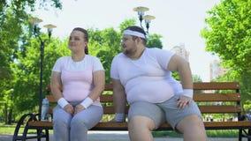 Homem novo gordo que coloca ao corrente com a senhora consideravelmente obeso que senta-se no parque, confiança filme