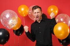 Homem novo gritando nos punhos de aperto clássicos pretos da camisa como o vencedor em balões de ar vermelhos do fundo ` S do Val foto de stock royalty free
