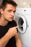 Homem novo infeliz com mashine de lavagem Fotografia de Stock