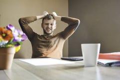 Homem novo irritado e funcionamento triste duro no documento e nas contas em casa imagens de stock