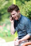 Homem novo irritado no telefone Fotos de Stock
