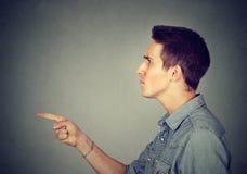 Homem novo irritado que aponta o dedo em alguém imagem de stock royalty free