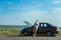 Homem novo irritado que espera uma ajuda ao sentar-se perto do carro quebrado foto de stock