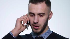 Homem novo irritado que fala em seu móbil Isolado no branco Conversa do homem novo ao telefone celular video estoque