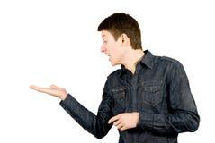 Homem novo irritado que olha a algo em sua mão Imagem de Stock Royalty Free