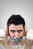 Homem novo irritado que tem a fita cinzenta do duto em sua boca Fotografia de Stock Royalty Free