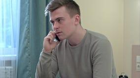 Homem novo irritado que tem um telefonema que senta-se na cama em casa Fotografia de Stock Royalty Free