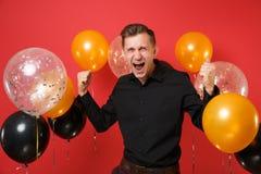Homem novo louco na camisa clássica preta que comemora, fazendo o gesto do vencedor, gritando em balões de ar vermelhos do fundo  foto de stock