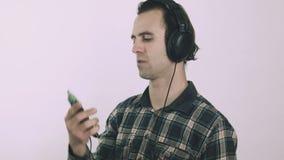 Homem novo louco que escuta a música alta em fones de ouvido video estoque