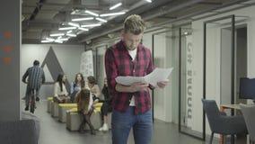 Homem novo louro pensativo que estuda os documentos de papéis que estão no escritório moderno Colegas fêmeas que conversam no filme
