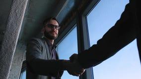 Homem novo moderno elegante com o homem de negócios da barba que agita as mãos com sócio Concluíram um negócio ou um contrato vídeos de arquivo