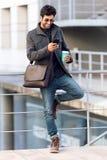 Homem novo moderno que usa seu telefone celular na rua Imagens de Stock Royalty Free