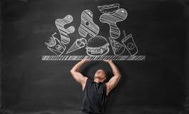 Homem novo Muscled que empurra fora da superfície com comida lixo e gordura foto de stock