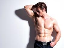Homem novo muscular considerável que olha lateralmente fotos de stock