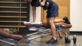 Homem novo muscular, CPE de formação no banco do gym vídeos de arquivo