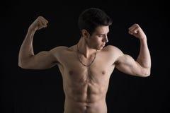 Homem novo muscular descamisado que faz o bíceps dobro fotografia de stock