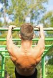Homem novo muscular durante seu exercício no parque Exercício da rua imagem de stock royalty free