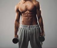 Homem novo muscular que dá certo com pesos Fotografia de Stock Royalty Free