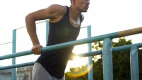 Homem novo muscular que faz exercícios em barras transversais paralelas fora, esporte imagem de stock royalty free
