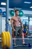 Homem novo muscular que levanta na sala da aptidão Foto de Stock