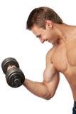 Homem novo muscular que levanta um dumbbell imagem de stock royalty free