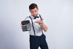 Homem novo não barbeado que mostra uma calculadora Imagem de Stock Royalty Free