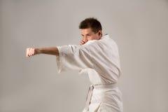 Homem novo na arte marcial branca do treinamento do quimono Fotografia de Stock Royalty Free